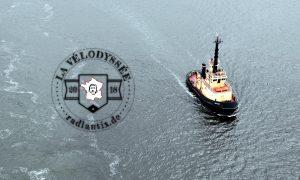 Von einer Brücke herab schaut man auf einen schwarz-weiß-rostigen ovalen Kutter im Meer. Das Bild trägt ein rundes Logo als Wasserzeichen.